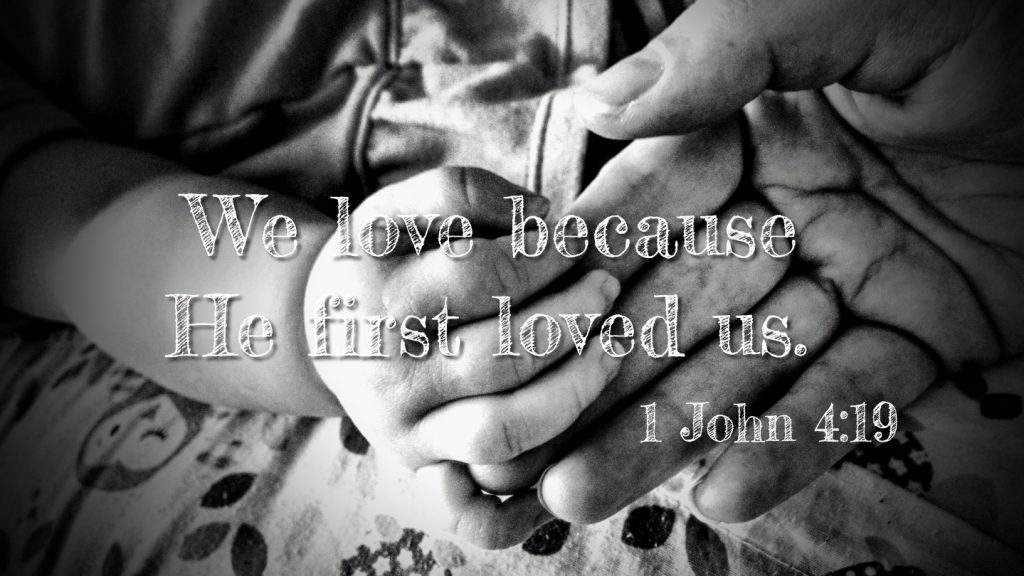 "Adult hand holding an infant's hand with text saying, ""We love because he first loved us. 1 John 4:19"""